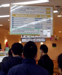 Standing in line at Family Mart on the 1st floor to buy a revenue stamp.